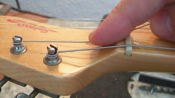 Beim Aufziehen der Saite kann mit dem Zeigefinger der rechten Hand die Saite auf Wickelhöhe herunter gedrückt werden.