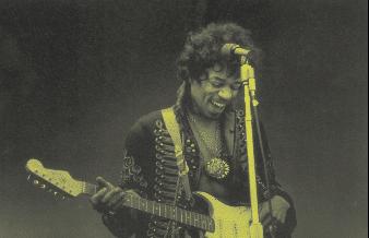 Jimi Hendrix lachend auf der Bühne mit Strat