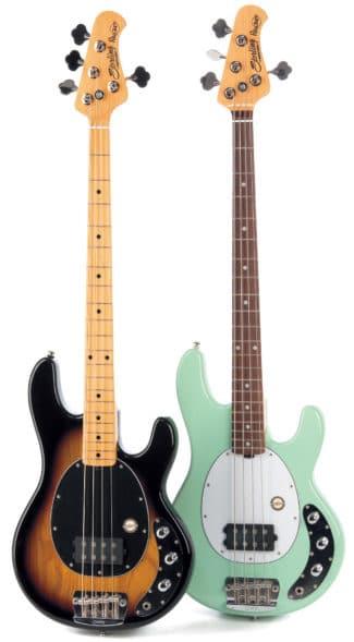 Zwei E-Bässe von Sterling, braun und weiß, stehend