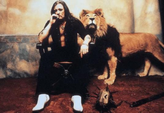 Lemmy Kilmister mit posiert mit einem Löwen im Hintergrund.