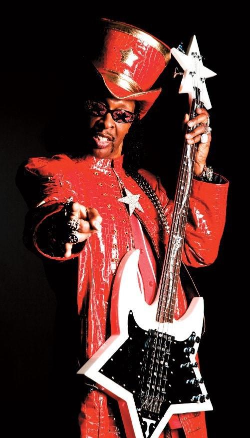 """Bootsy Collins ist auffällig mit rotem Mantel, Hut und Sonnenbrille gekleidet und hält den sternenförmigen """"Star Bass"""" in der Hand."""