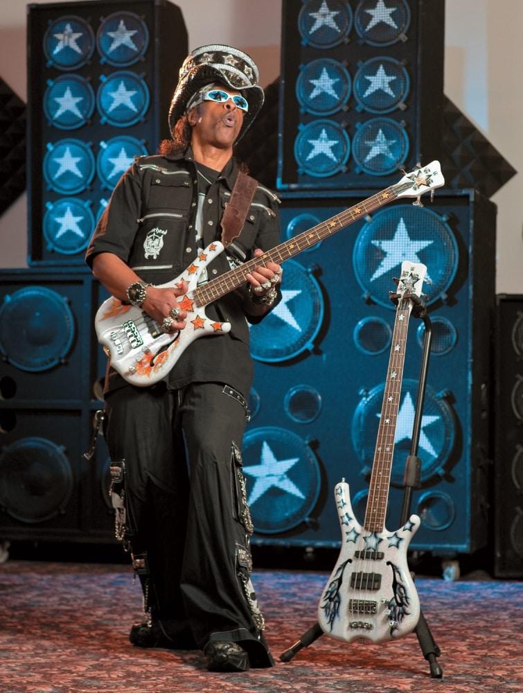 Bootsy Collins mit großem Hut und Sonnenbrille spielt einen Warwick Infinity-Bass. Daneben steht ein weiterer Bass auf dem Boden.