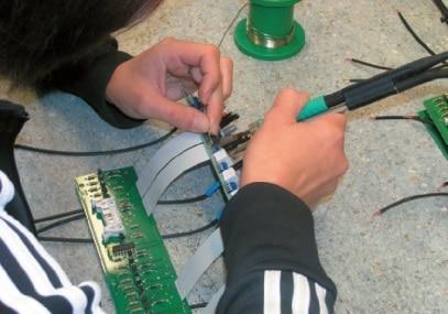 Ein Flachbandkabel wird per Hand eingelötet.