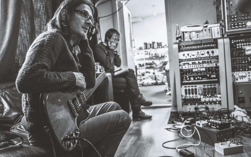Steven Wilson with a guitar in the studio