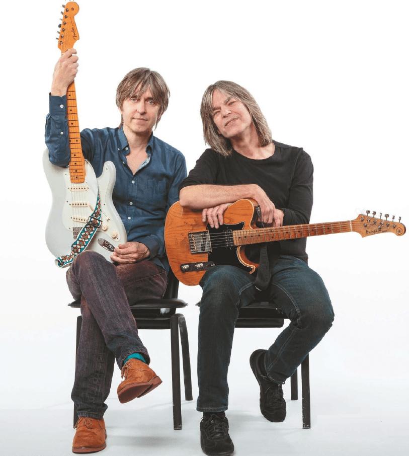 Eric Johnson und Mike Stern sitzen auf zwei Stühlen mit ihren Gitarren